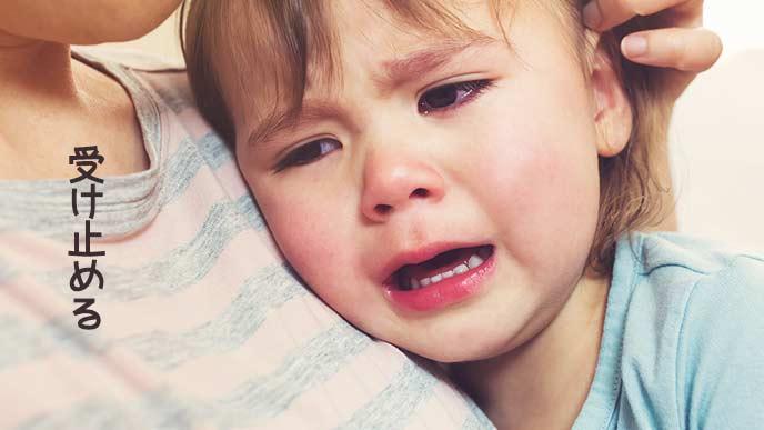 泣く子供を抱く母親