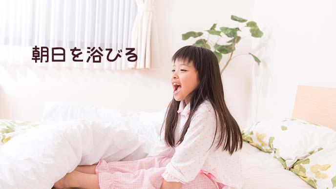 ベッドの上で体を起こして窓の方を見る女の子