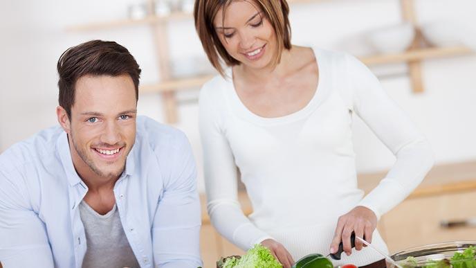 調理する妻の隣で見守る夫