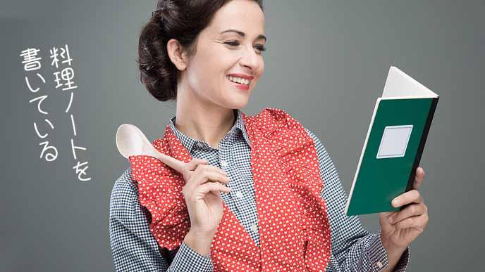 料理ノートを見ながら笑顔のエプロンを着た女性