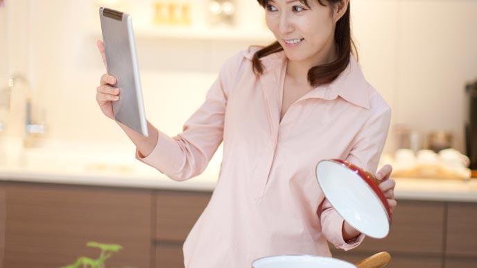 タブレットを見ながら好きな料理研究家のレシピをつくる女性