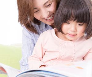 母親と本を読む4歳児