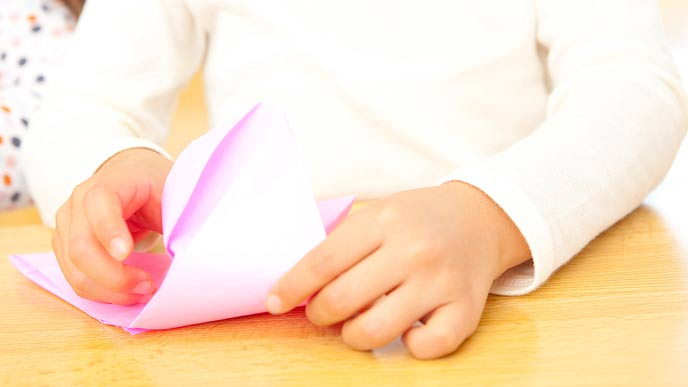 折り紙を折る子供の手