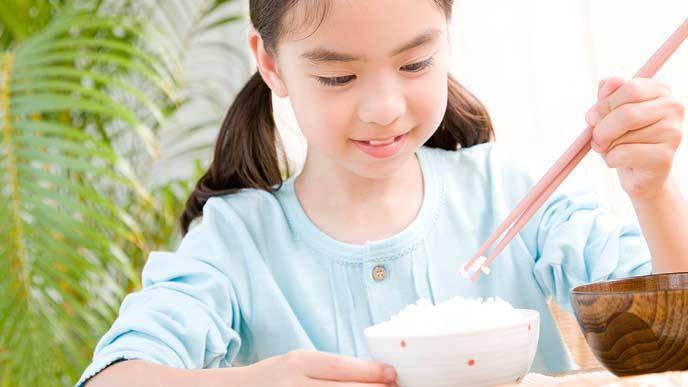 朝食のご飯を食べる小学生