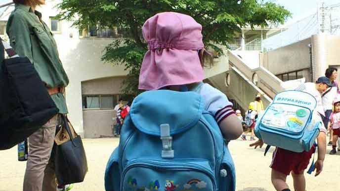 幼稚園に集合するリュックを背負った子供たちと見守る親