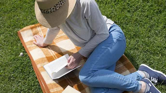 ジーパンと長袖と帽子の服装で草地で休憩する女性