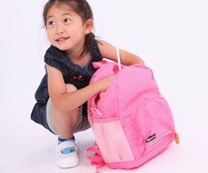 ピンク色のリュックの中身を見る女の子
