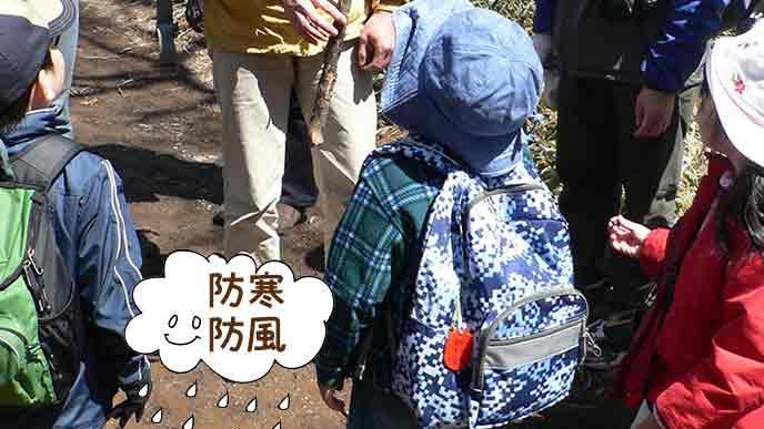 ウィンドブレーカーを着て帽子を被った子供たち