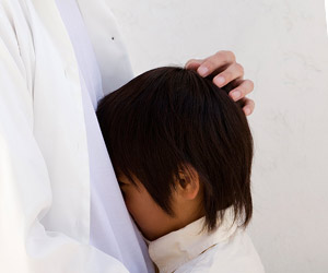 親の胸に顔を埋めて離れようとしない子供