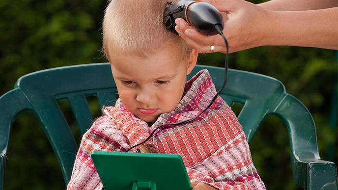 バリカンで髪を切ってもらってる男の子