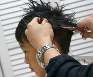 美容院で髪を切ってもらっている男の子