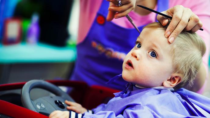 美容室で車の形のカットチェアに座って髪を切ってもらってる男の子