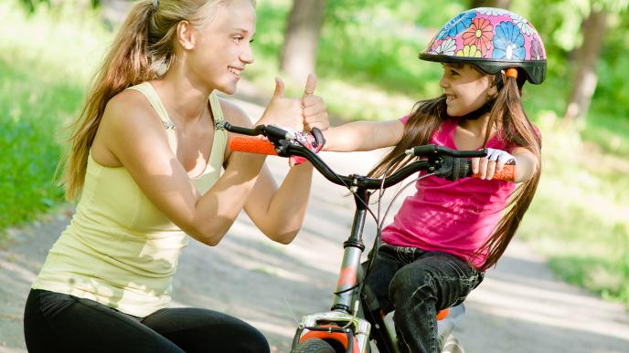 自転車に上手く乗れて母親に褒められ笑顔の女の子