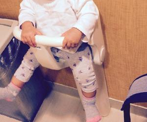 公衆トイレに設置されてるベビーチェアに座ってる幼児