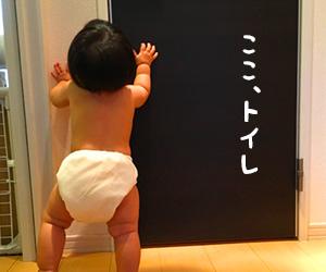 トイレのドアに掴まって立ってるオムツを履いた子供