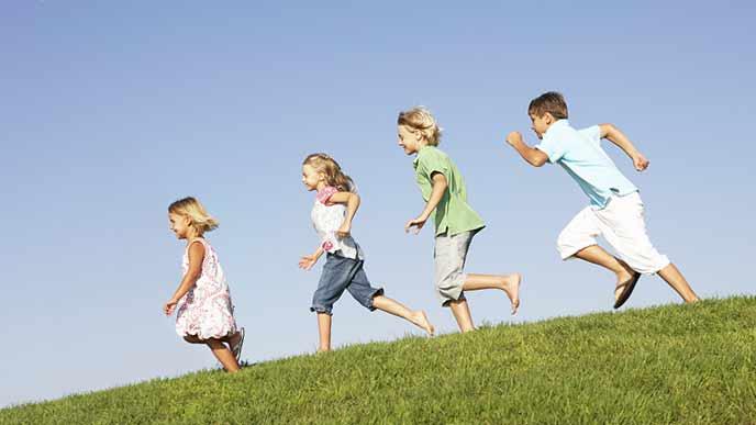 子供たちが並んで土手を下りていく