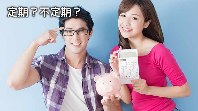 貯金箱と電卓を持って並んで立つ夫婦