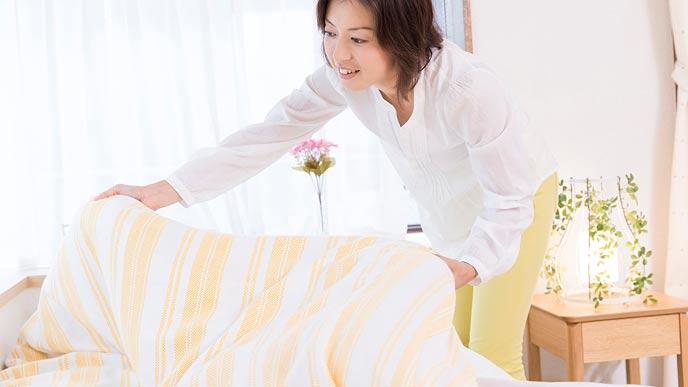 ベッドの布団を整えてる奥さん