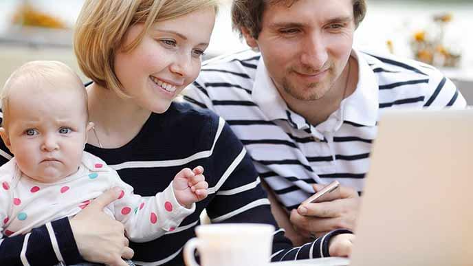 赤ちゃんを抱えながらノートパソコンを見る主婦と夫