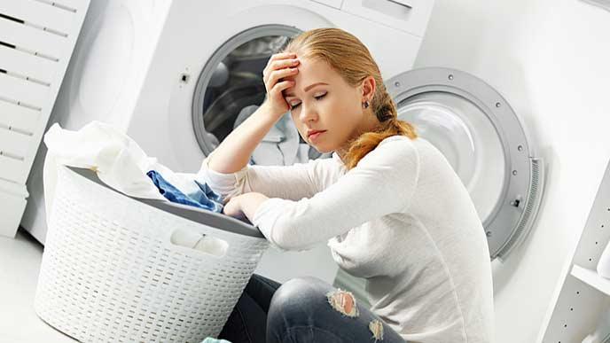 疲れて洗濯籠に寄りかかる主婦
