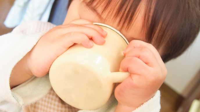 寝る前にコップでジュースを飲んでる小学生の男の子