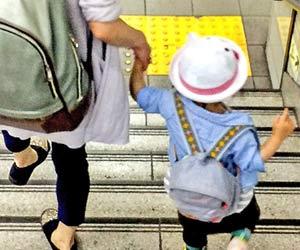 子供の手を引いて駅の階段を下りる母親