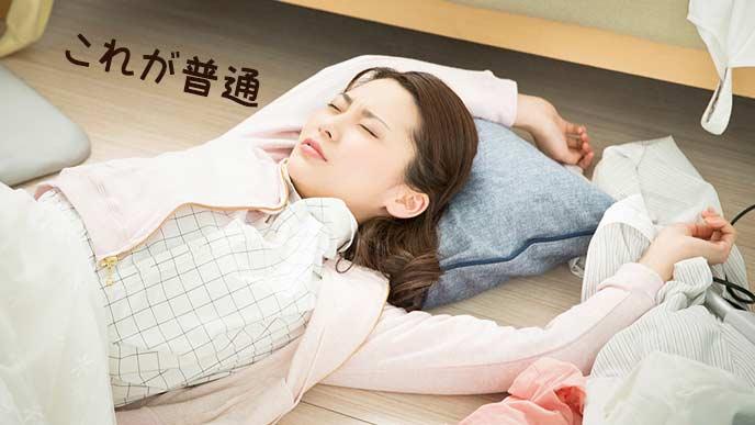 床に散らかるモノの中で昼寝する女性