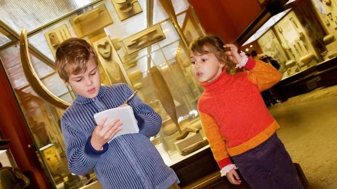 博物館に社会科見学でメモをとってる小学生