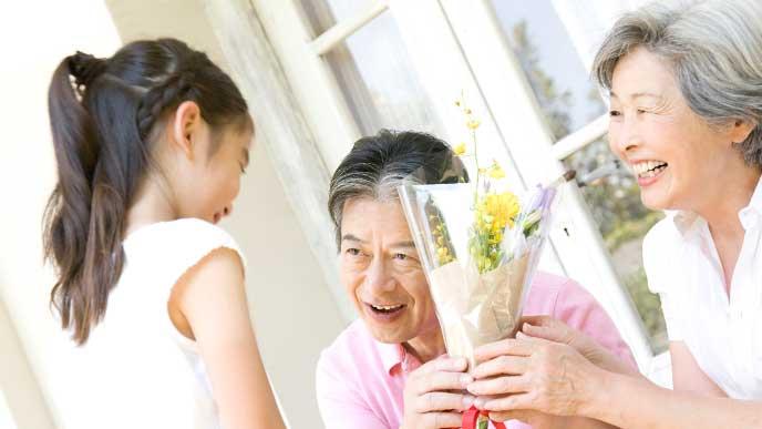 老人ホームの利用者に花束を渡す小学生の女の子