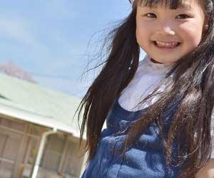 幼稚園の中庭に立つ女の子
