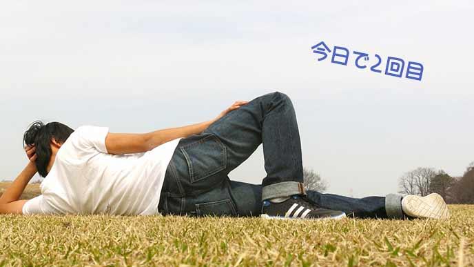 ジーンズで芝生に横になる男性