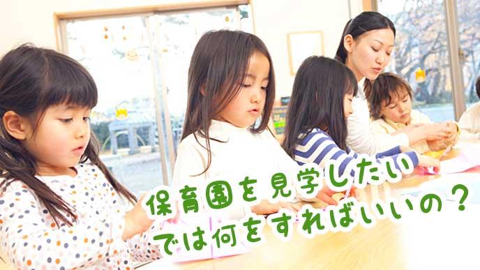 保育園の先生と一緒に折り紙で工作をする園児たち