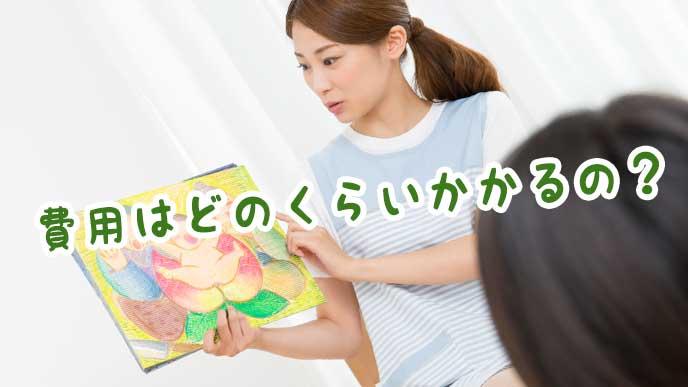 一時保育の園児に桃太郎の紙芝居でお話をする保育園の先生