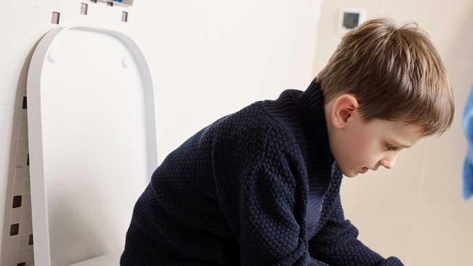 便座に座りトイレトレーニングをしている男の子