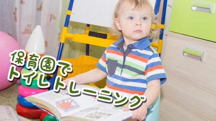 保育園で本を見ながらオマルに座ってる男の子
