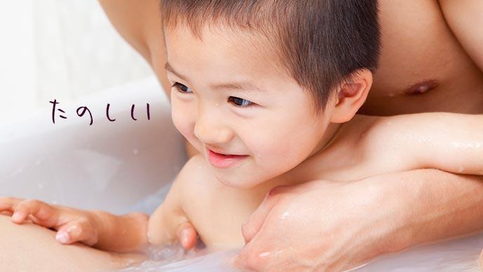 父親と一緒に笑顔でお風呂に入る子供