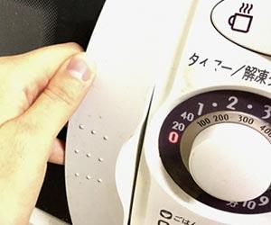 電子レンジで調理する妻の手