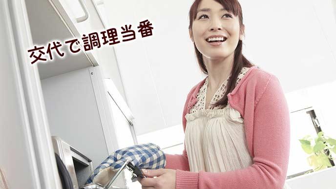 オーブンから料理を取り出す主婦