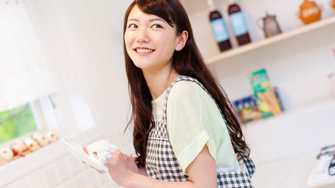 台所で皿を拭く妻