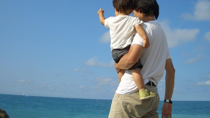 息子を抱きあげて海を見せる父親