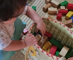 積み木の入ったカゴの中に手を入れる子供