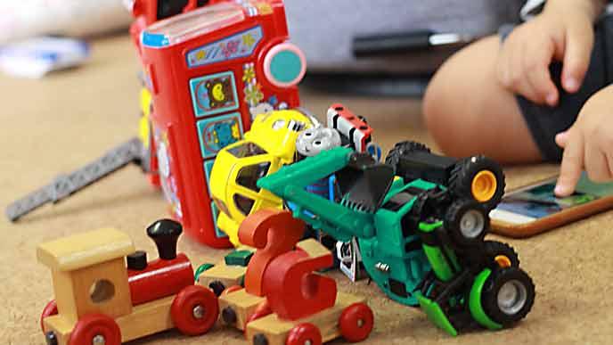 車の玩具を床に並べて遊ぶ子供