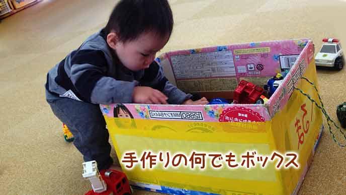 段ボールの何でもボックスに玩具をしまう子供