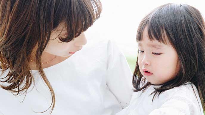 泣く娘をあやす母親