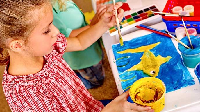 黄色い魚の絵を描く女の子
