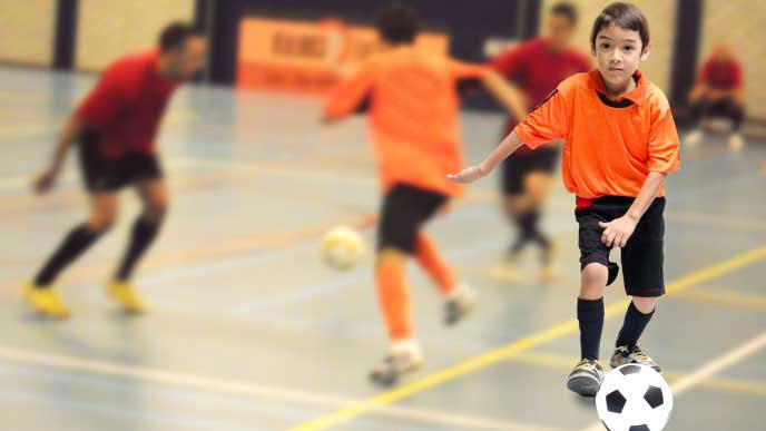 体育館の中でサッカーをしている小学生達
