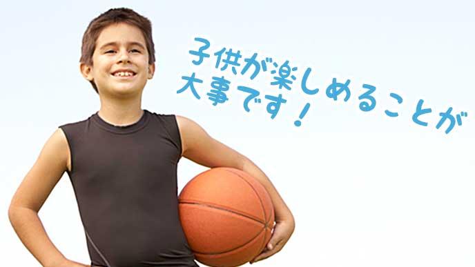 笑顔でバスケットボールを持つ少年