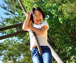 アスレチック施設で遊ぶ少女