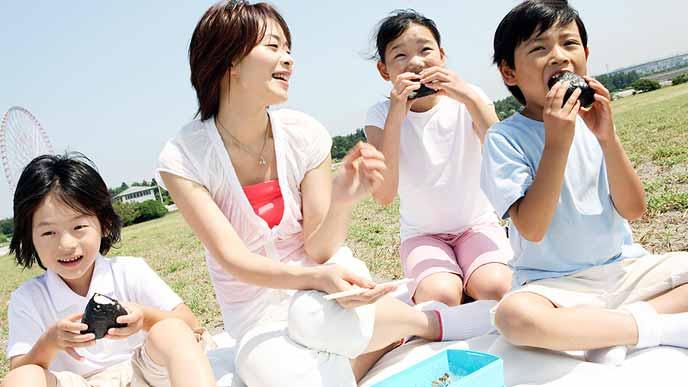 公園で芝生の上でおにぎりを食べる家族