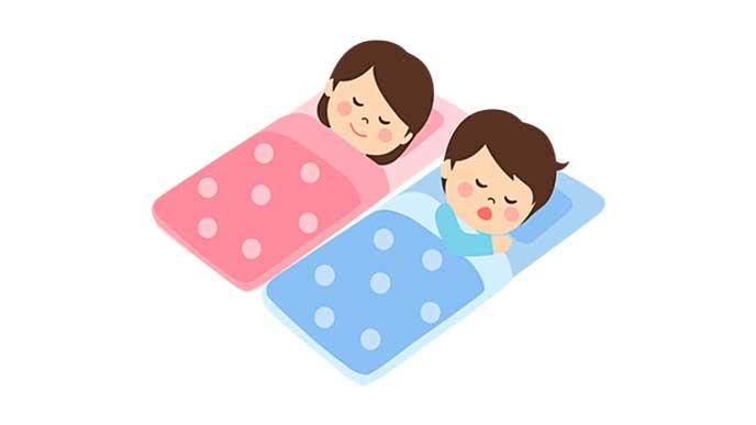 布団をかけてお昼寝する保育園児